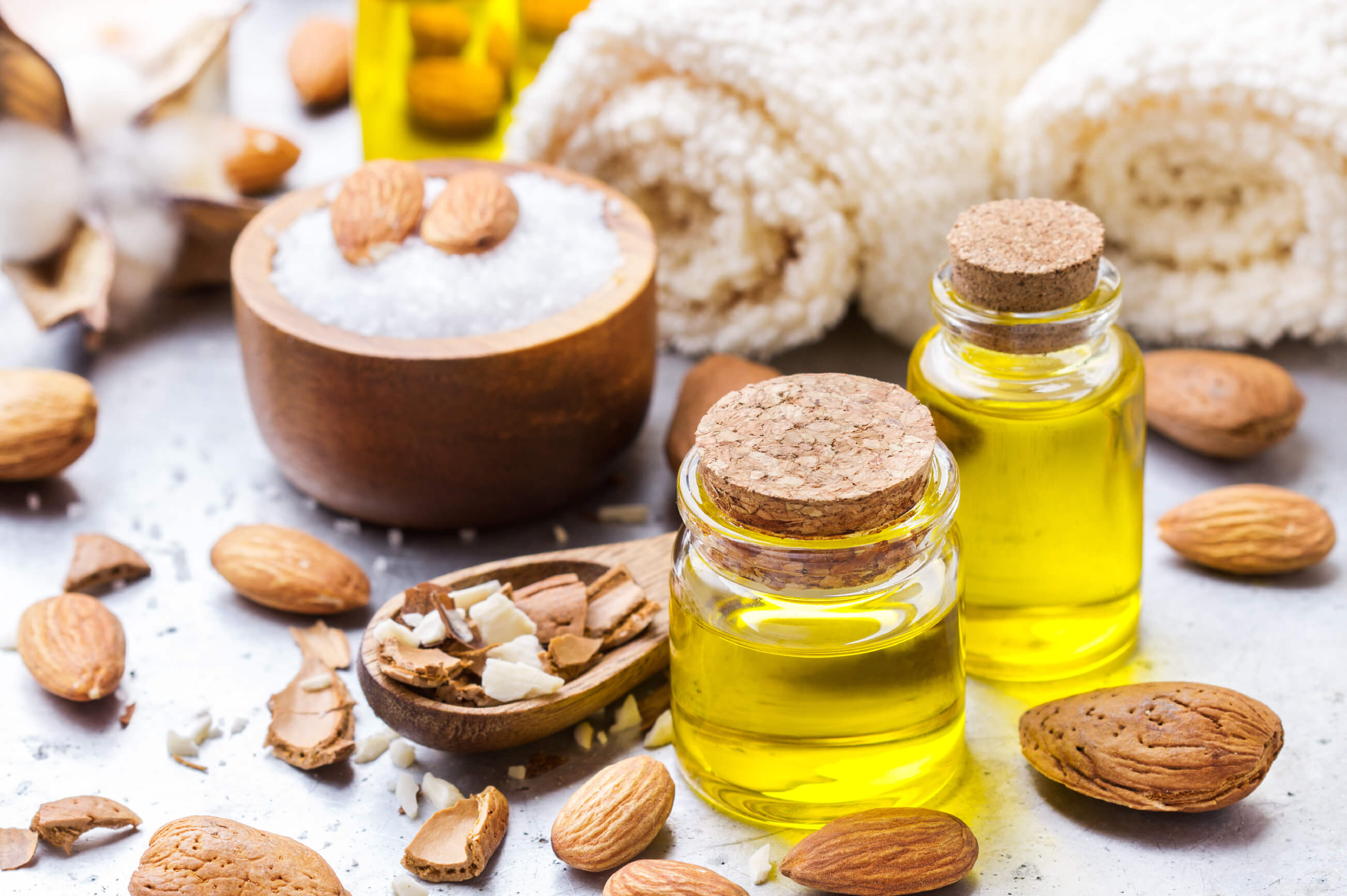 Two small jars of almond oil surrounded by loose almonds